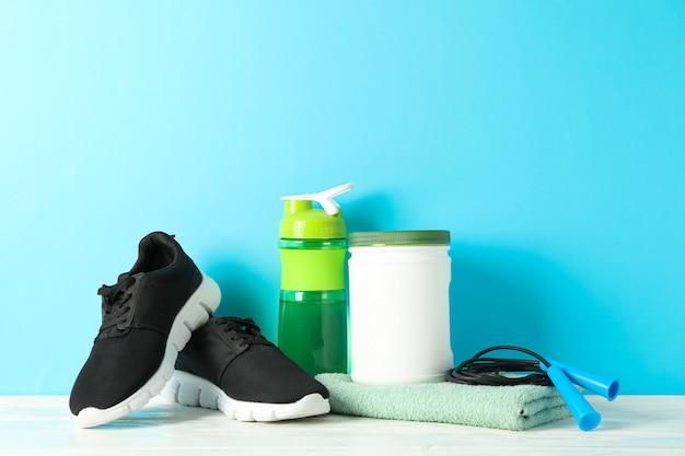 De toebehoren van de sportlevensstijl op witte houten lijst tegen blauwe achtergrond