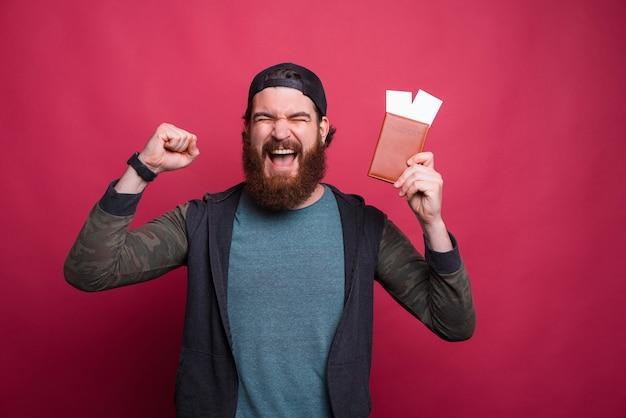De toejuichende gebaarde mens houdt paspoort met kaartjes terwijl het maken van winnaargebaar