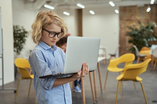 De toekomst ervan portret van een kleine geniale jongen met een bril die een laptop vasthoudt en gebruikt terwijl hij poseert