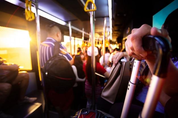 De toerist bacpacker houdt zijn bagage en mobiel op bus voor vervoer van luchthaven eindpoort naar vliegtuig.
