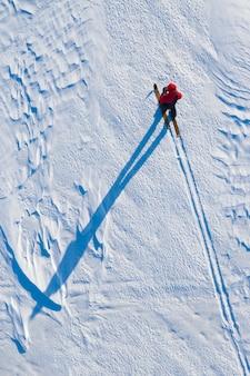 De toerist beweegt zich op ski's op de noordpool in de winter wordt van bovenaf uit de helikopter gehaald
