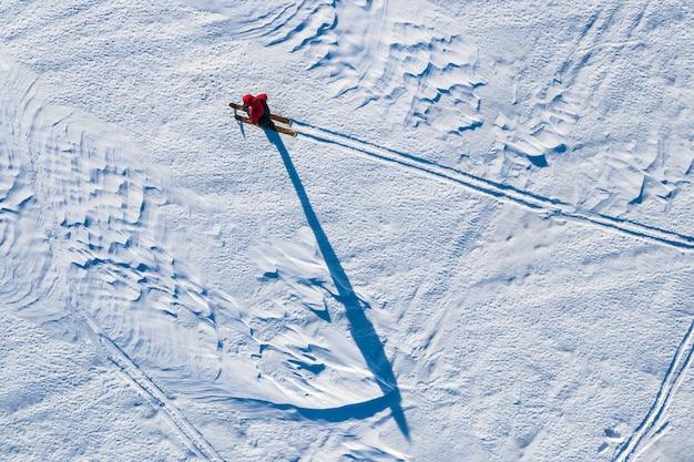 De toerist beweegt zich op ski's op een met sneeuw bedekt veld in de winter wordt van bovenaf uit de helikopter gehaald