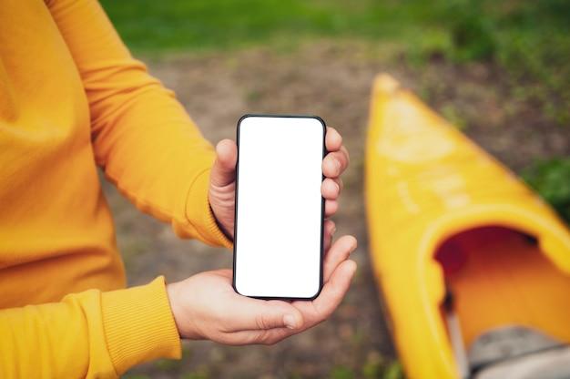 De toerist heeft een telefoon in zijn handen. bespotten smartphone close-up op de achtergrond van een kajak en een meer.