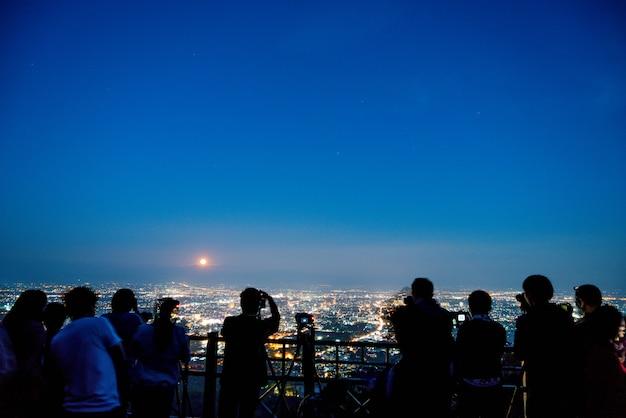 De toerist neemt een foto met chiang mai, de stadshorizon van thailand en machtsmaan op de hemel