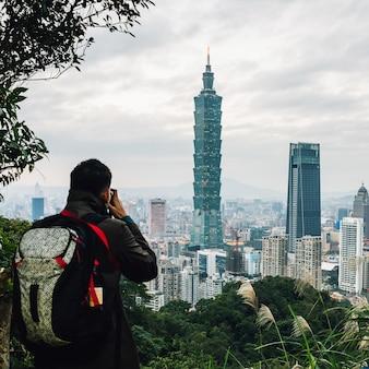De toerist neemt een foto van luchtpanorama over taipeh van de binnenstad met taipeh 101 wolkenkrabber in de schemer.