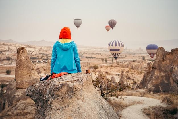 De toerist ontmoet zonsopgang in cappadocia met luchtballon in hemel