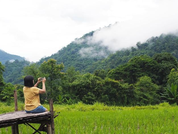 De toerist van de vrouw zittend op houten voetpad en het nemen van foto van berg en padieveld