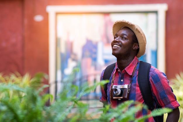 De toeristen afrikaanse mens voelt zich gelukkig met reisplaats in landschapsstad.