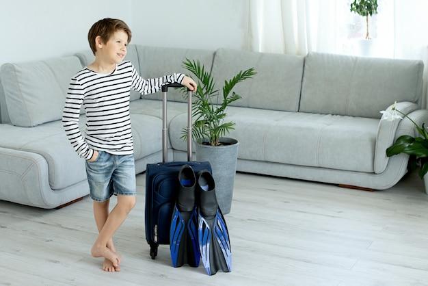 De toeristenjongen met een koffer en vinnen blijft thuis