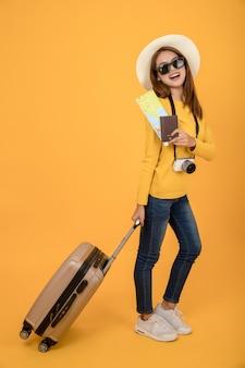 De toeristenvrouw van de reiziger in de zomerdraagkleding die over gele achtergrond wordt geïsoleerd