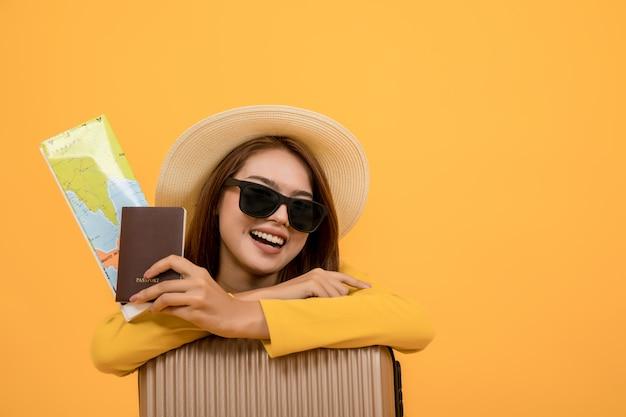De toeristenvrouw van de reiziger in de zomerkostuums, het paspoort van de vrouwenholding met kaart, hoed en zonnebril die weg over gele achtergrond wordt geïsoleerd