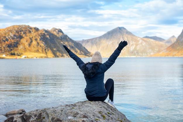 De toeristenzitting van de vrouw op rots in het landschap van noorwegen
