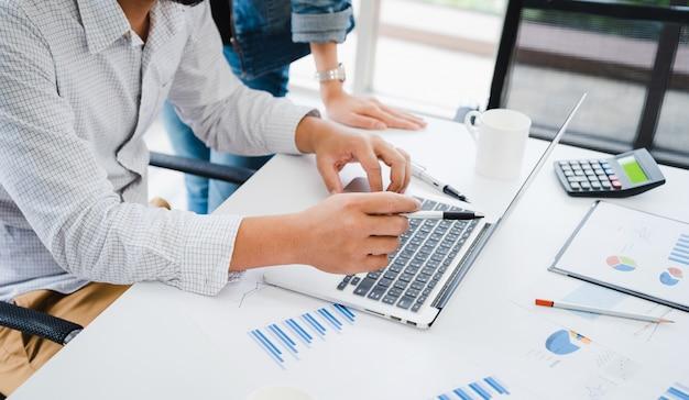 De toevallige zakenman bespreekt over marketing plan op laptop aan team met bedrijfsgrafiekdocument op lijst