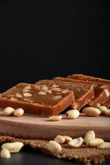 De toffee van het pindahuis op een houten raad. plakjes oosterse snoepjes met noten.
