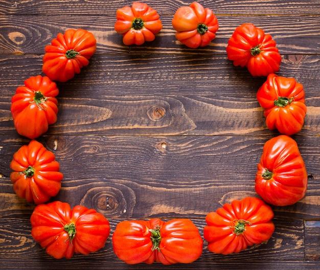 De tomaten van het oshart op rustieke houten vrije ruimte als achtergrond voor tekst.