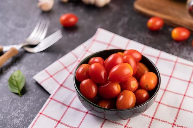De tomaten zitten in de zwarte beker