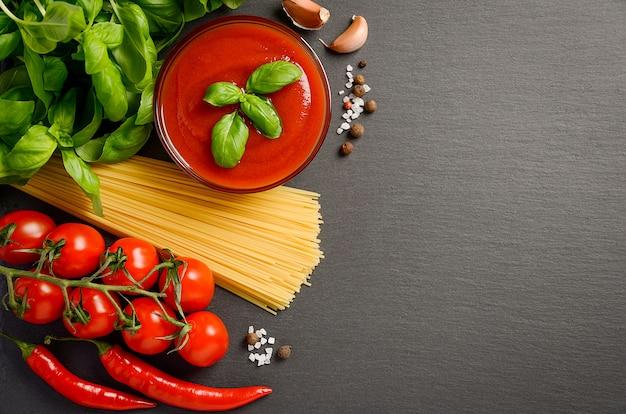 De tomatensaus met deegwaren op zwarte achtergrond, hoogste vlakke mening, legt, kopieert ruimte.