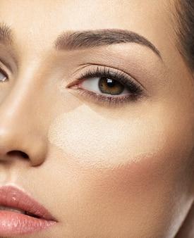 De tonale foundation van de cosmetische make-up is op het gezicht van de vrouw. huid zorg concept.