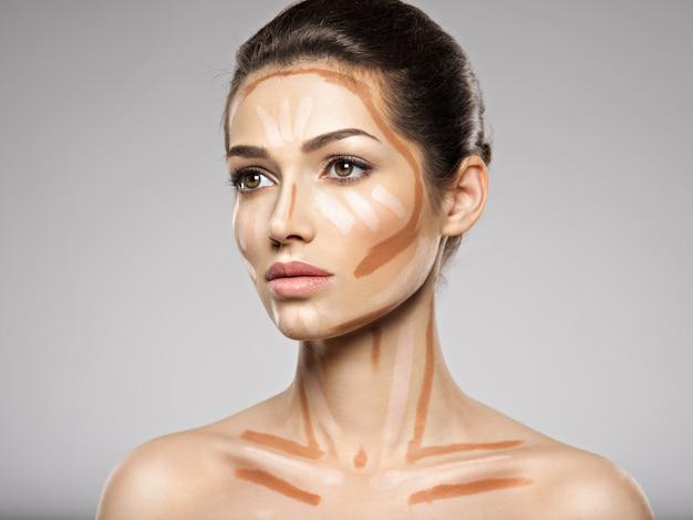 De tonale foundation van de cosmetische make-up is op het gezicht van de vrouw. schoonheidsbehandeling concept. meisje maakt make-up.