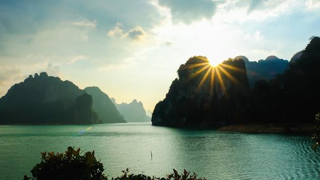 De toneellandschapsmening van het watergolven van het aardoever van het meer en zonlichtgloed door over bergen belde achtergrond in cheow lan dam (ratchaprapa-dam) in suratthani thailand.