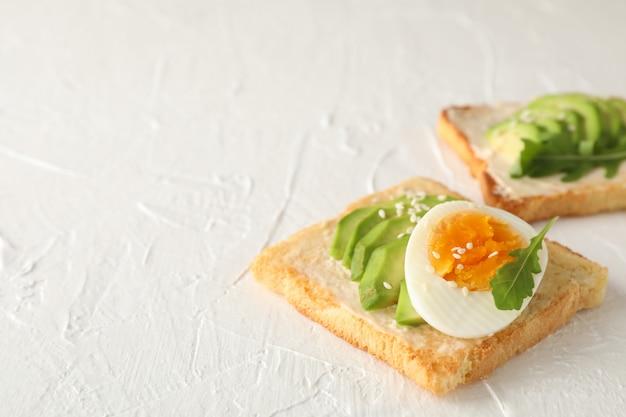 De toosts met avocado en ei op witte achtergrond, sluiten omhoog