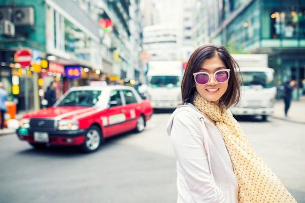 De toothy het glimlachen emotie van het gezichtsgeluk van aziatische vrouw die zich op de stadsstraat van hongkong bevinden