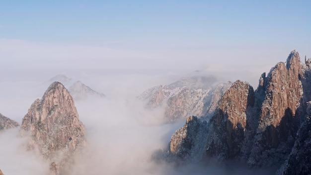 De toppen van de bergen en daaronder de wolken