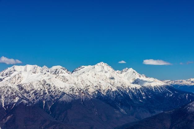 De toppen van de besneeuwde bergen op de achtergrond van de blauwe lucht