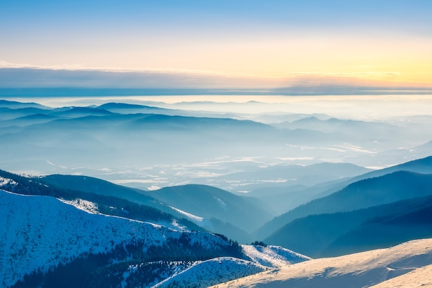De toppen van winterbergen en lichte mist in de valleien. zonnig weer en blauwe lucht