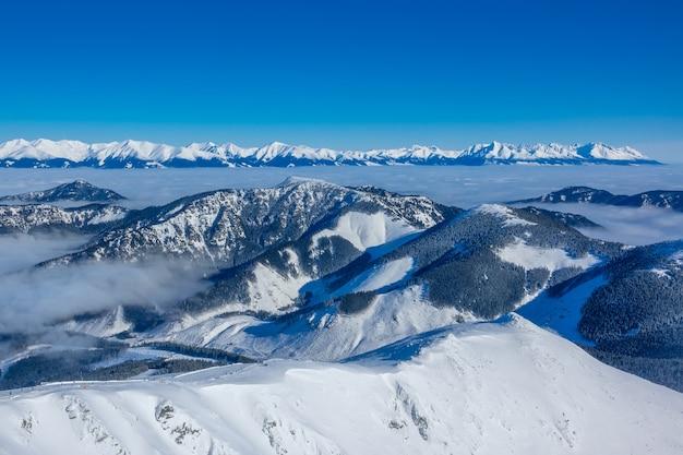 De toppen van winterbergen en ochtendmist in de valleien. zonnig weer en blauwe lucht