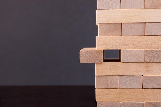De toren is gebouwd van houten blokken voor planning. een beslissingsspel dat concentratie vereist. bedrijfsconcept.