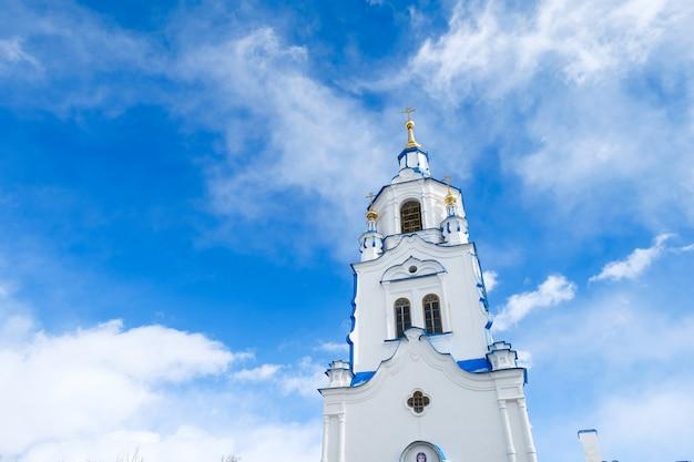 De toren van de kerk op de achtergrond van de blauwe lucht met wolken. rusland, tyumen.