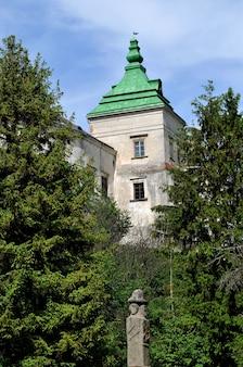 De toren van een middeleeuws huis temidden van groene bomen