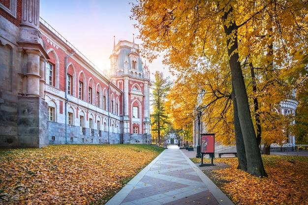 De toren van het tsaritsyno-paleis in moskou en de gouden bomen van het steegje in het park op een zonnige herfstochtend