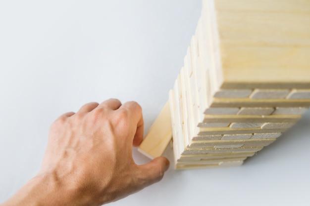 De toren van houten blokken en de hand van de mens nemen een blok. het spel van dobbelstenen op een witte tafel. het uitzicht vanaf de top