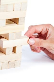 De toren van houten blokken en de hand van de mens nemen een blok