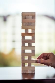 De toren van houten blokken en de hand van de mens nemen één blok