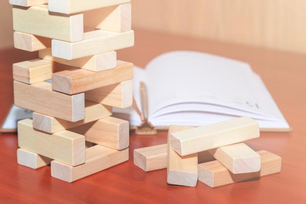 De torenstapel van houten blokken, ernaast ligt een notitieboekje met een pen. bedrijfs- en bouwconcept.