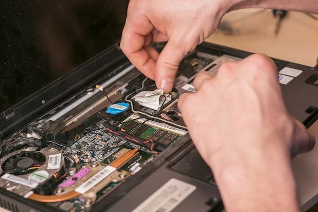 De tovenaar repareert de laptop. demontage van de laptop voor reserveonderdelen. onderhoud van computerapparatuur met behulp van tools. binnenaanzicht van de laptop