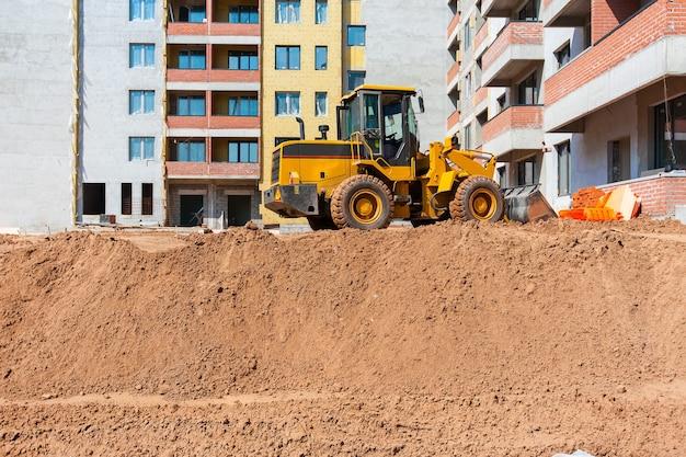 De tractor egaliseert de grond op de bouwplaats earthworks
