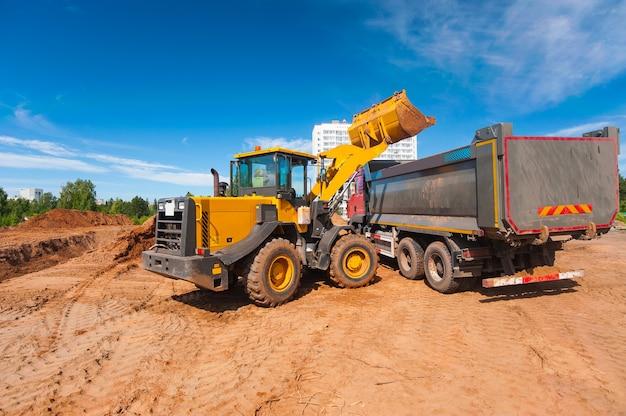 De tractor laadt de grond in de kiepwagen wegenreparaties