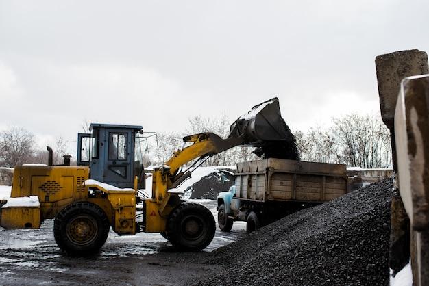 De tractor laadt kolen in de vrachtwagen.
