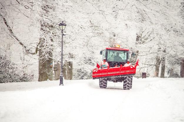 De tractor maakt weg van sneeuw in de winter schoon