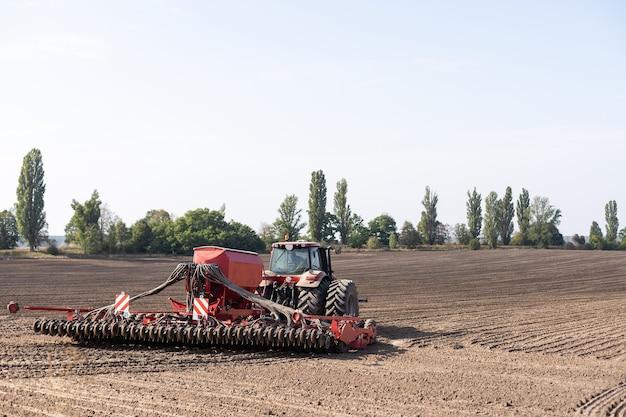 De tractor-oogstmachine aan het werk op het veld