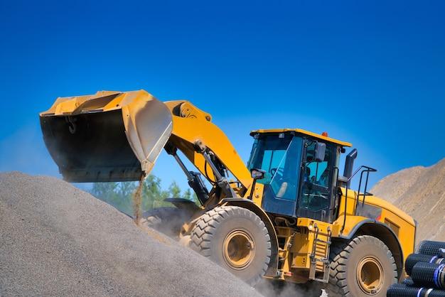 De tractor verzamelt een schep met grind