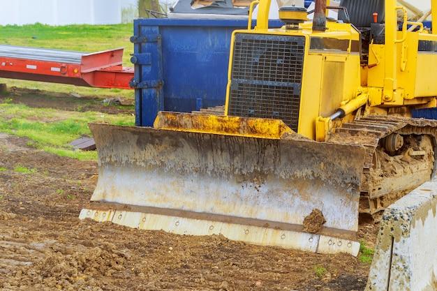 De tractorgraver, op zwaar werk berekend bouwmateriaal dat wordt geparkeerd