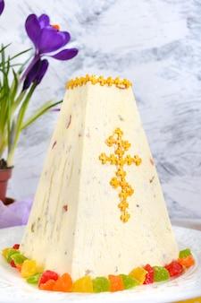 De traditionele cake van gestremde melkpasen met gekonfijte vruchten en de krokus van de lentebloemen op de vakantie lichte achtergrond.