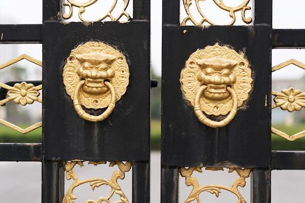 De traditionele chinese oude rode deur van de architectuurdeur en gouden leeuw.