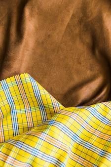 De traditionele geruite stoffentextuur op bruin drapeert textiel