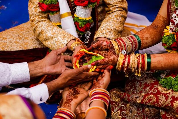 De traditionele indische huwelijksceremonie, bruidegomholding dient bruidhand in